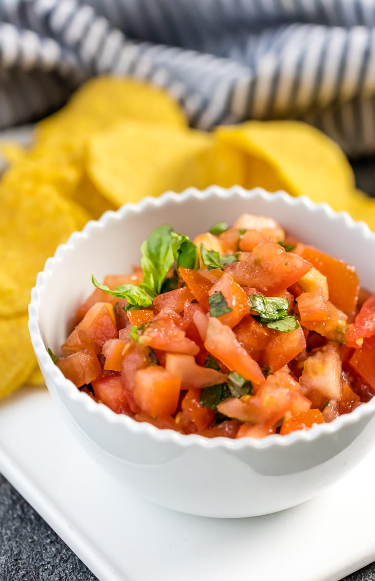 Italian salsa in white bowl with tortilla chips.
