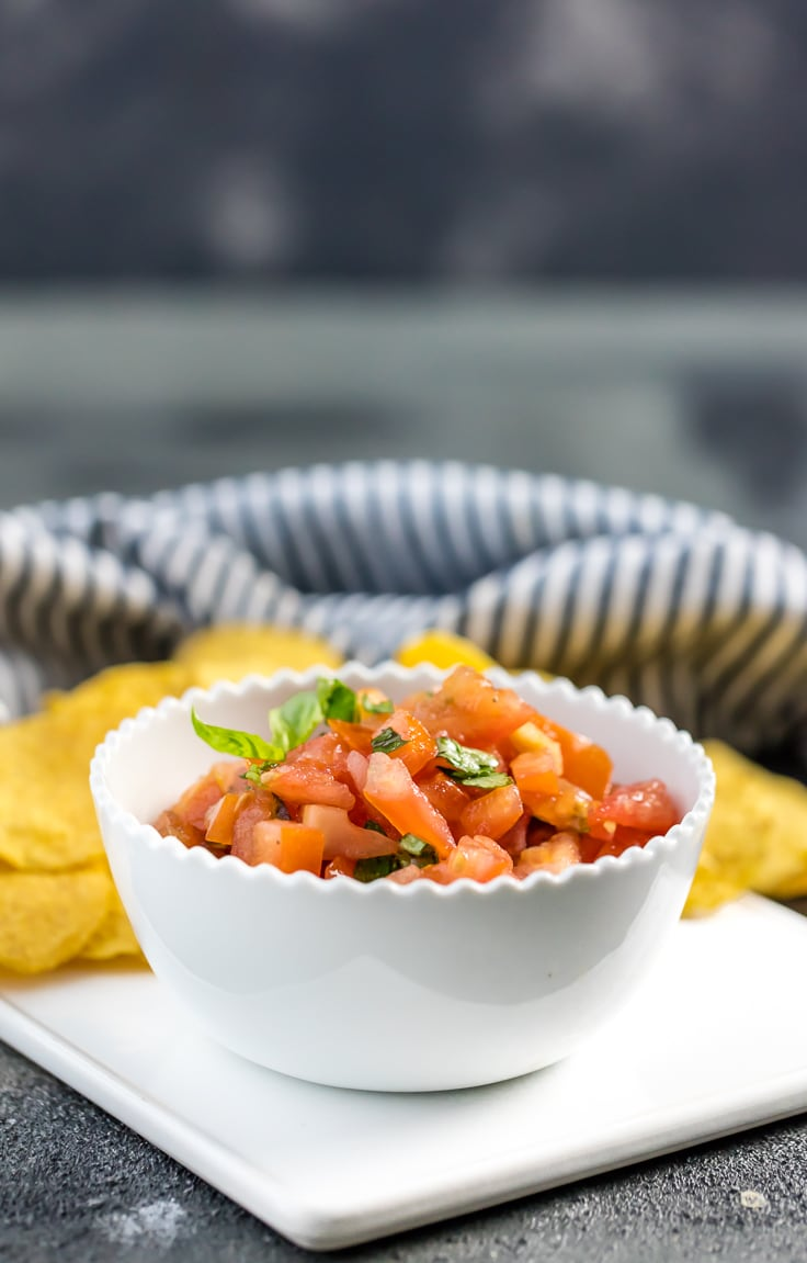 Italian salsa in white bowl with striped towel in background.