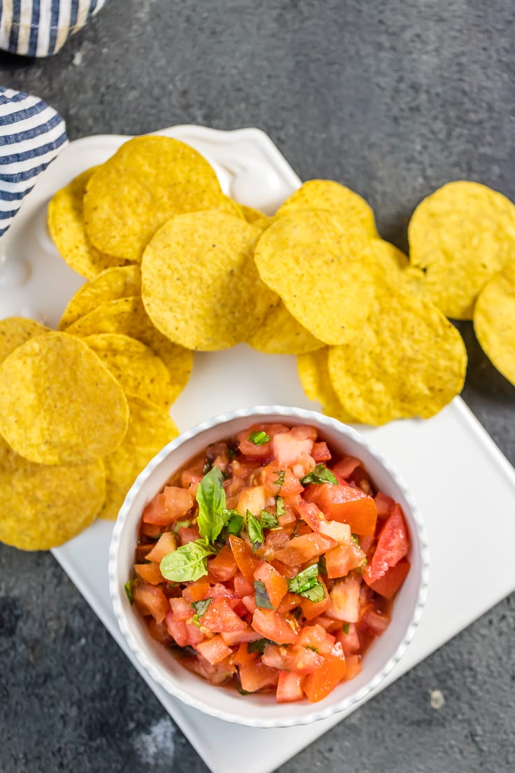 Italian salsa with tortilla chips on white plate