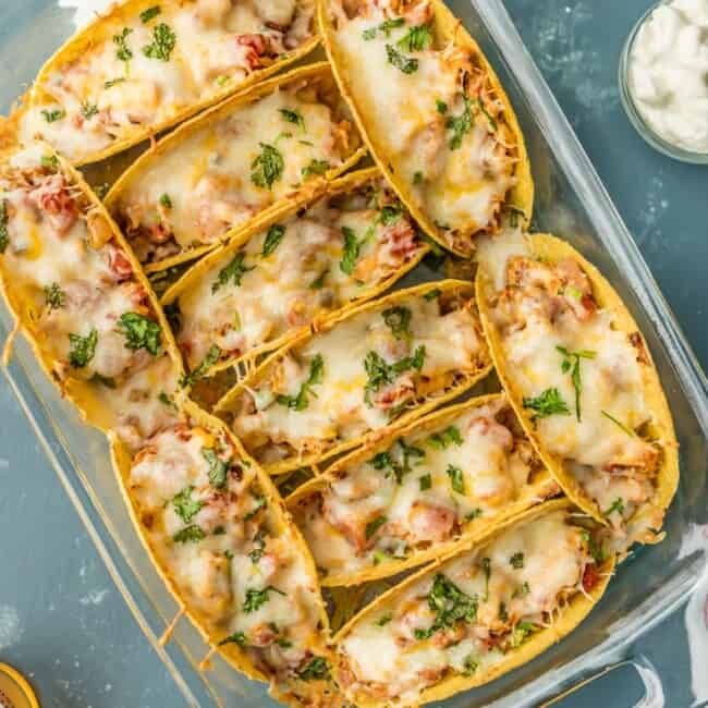 SUPER EASY Oven Baked Spicy Chicken Tacos make a weekly appearance on our table. All the flavor and none of the stress. ALL THAT MELTED CHEESE! Perfect Chicken Tacos recipe for a crowd on Family Mexican Night!