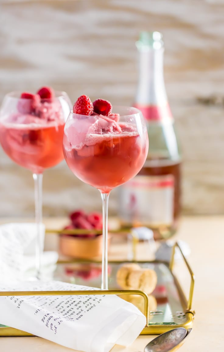 two wine glasses filled with raspberry champagne floats