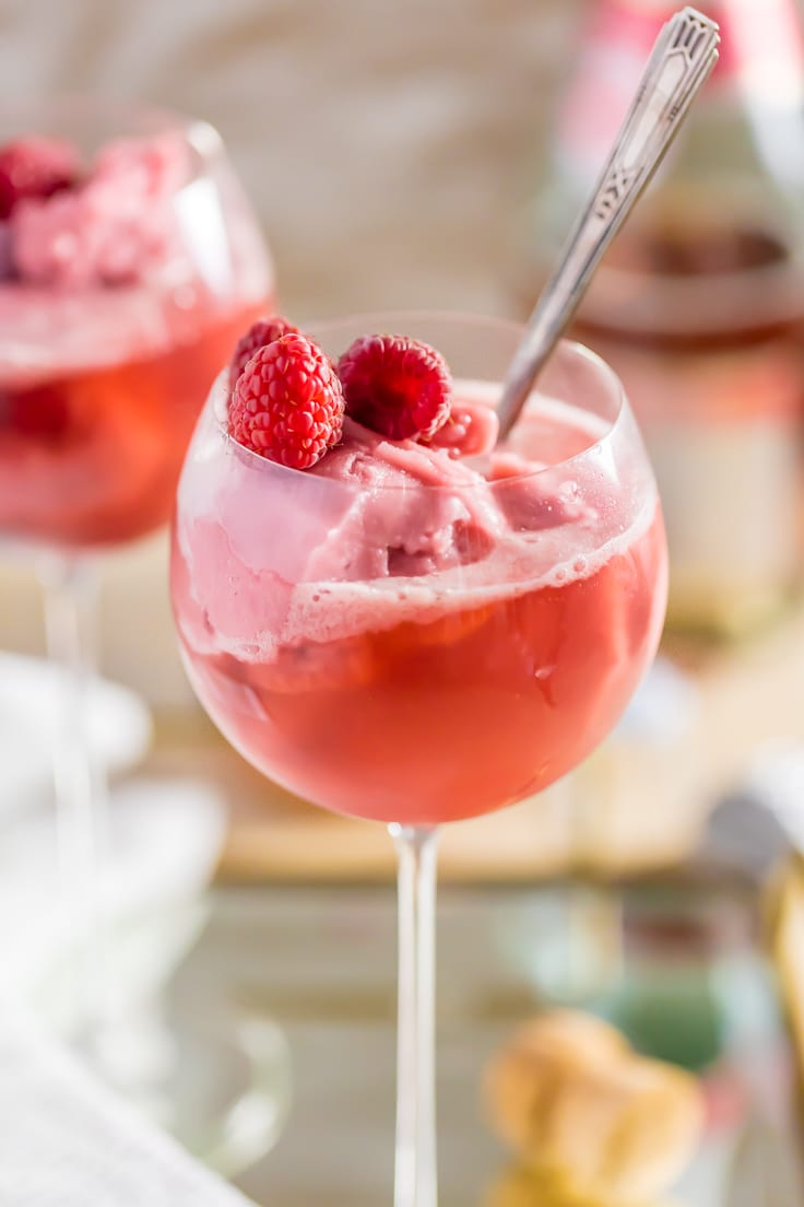 close up on a wine glass filled with raspberry sorbet and pink champagne, with a silver spoon stuck in it