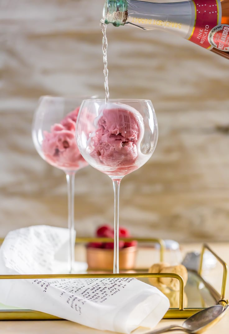 pouring pink champagne into a glass filled with raspberry sorbet