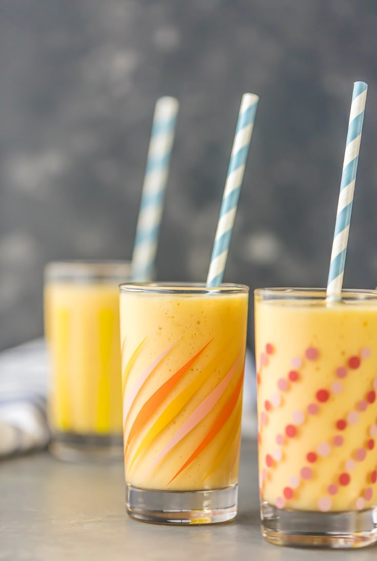 three simple mango smoothies with straws