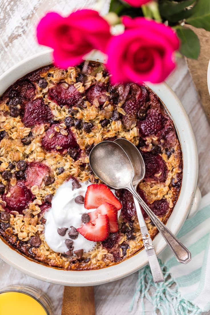 chocolate covered strawberry baked oatmeal recipe in a large white dish with two spoons