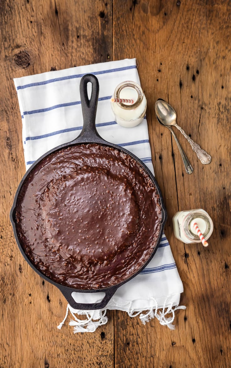 a skillet filled with chocolate cake sitting on a striped dish towel, with two small jars of milk and two spoons