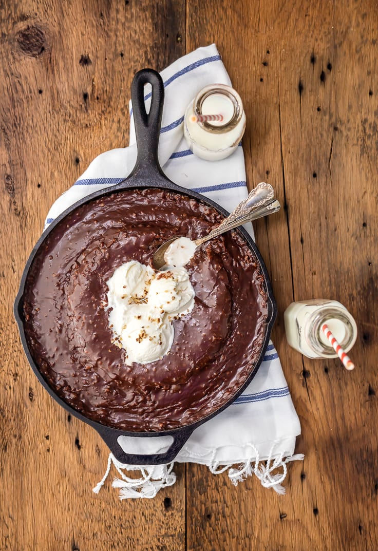 chocolate cake in a skillet next to two jars of milk