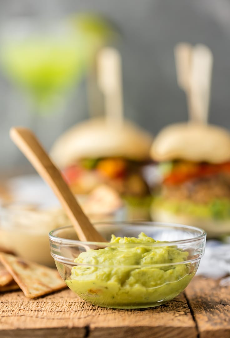 a bowl of guacamole, with veggie sliders in the background