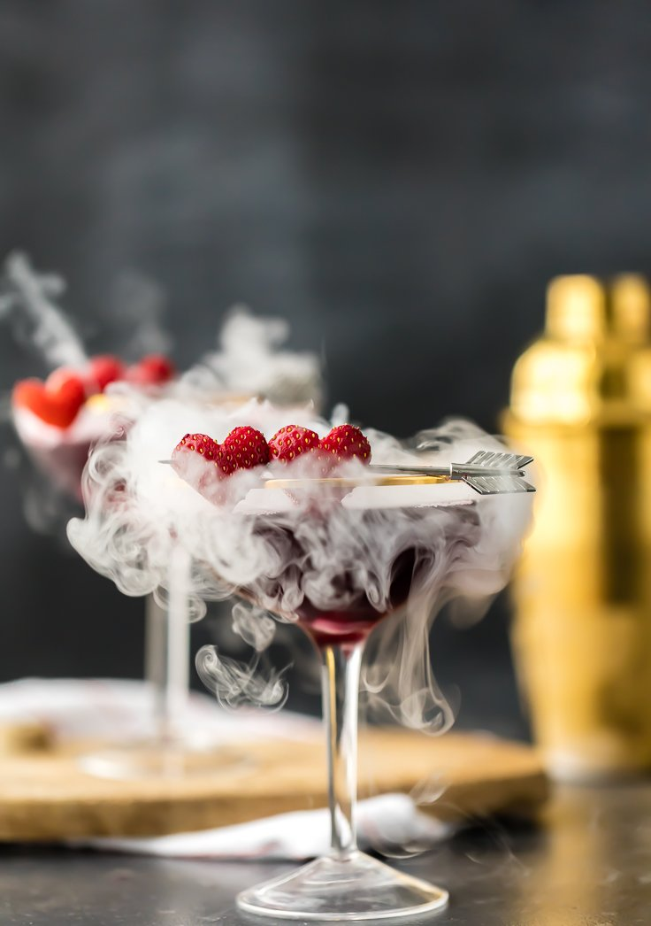 two berry pomegranate martinis with dry ice smoke wafting out