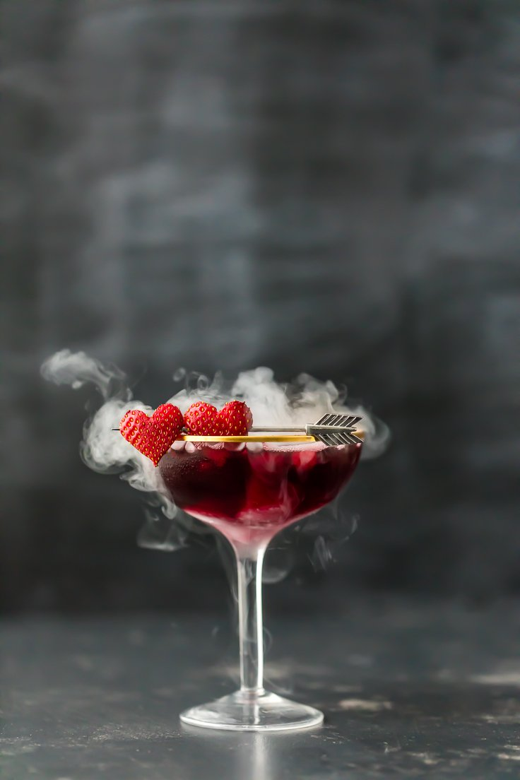 a purple martini in a glass with heart shaped strawberries and dry ice