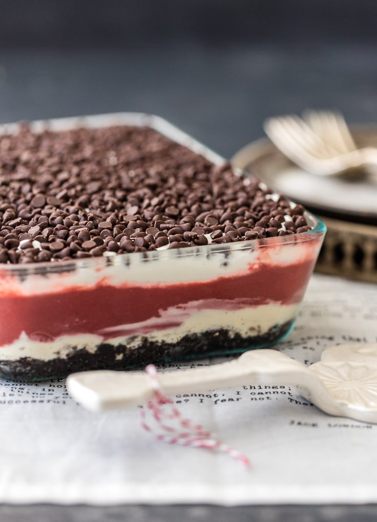 Layers of whipped cream, cheesecake, chocolate pudding, oreos, and more in a glass baking dish