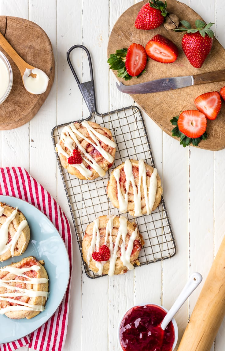 strawberry cinnamon roll cookies on a cooling rack, surrounded by plates of cookies and strawberries