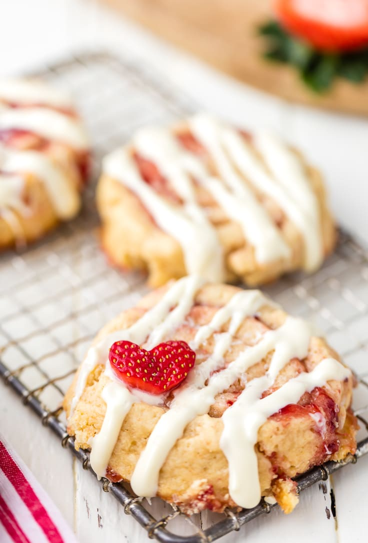 cinnamon roll cookies topped with icing and strawberry hearts