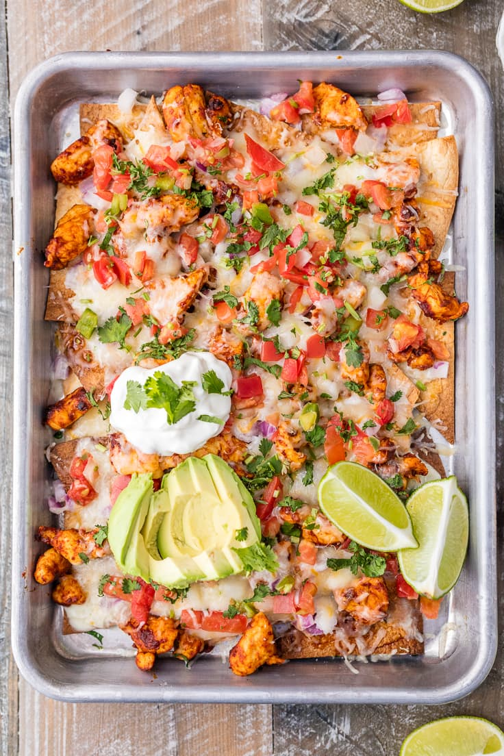 This Chicken Nachos Recipeis a great recipe for feeding a crowd with delicious chicken nachos! These Tequila Lime Baked Chicken Nachos are AMAZING! This easy sheet pan recipe is delicious, and perfect for any occasion.