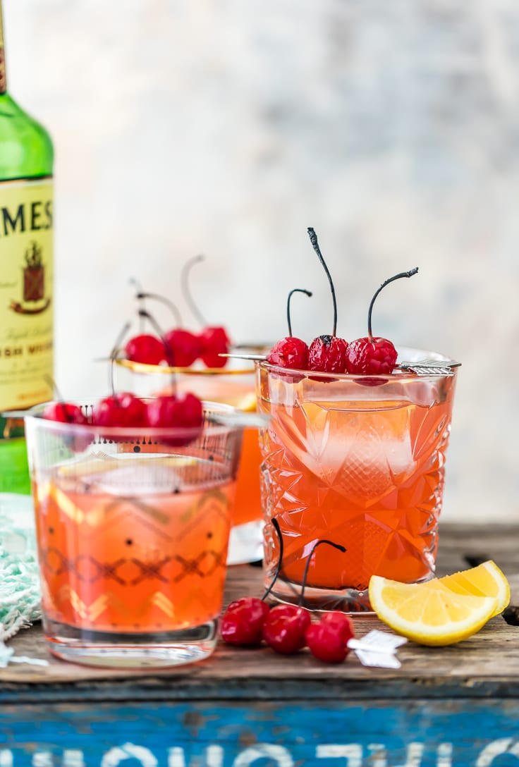 whiskey sours garnished with broiled cherries