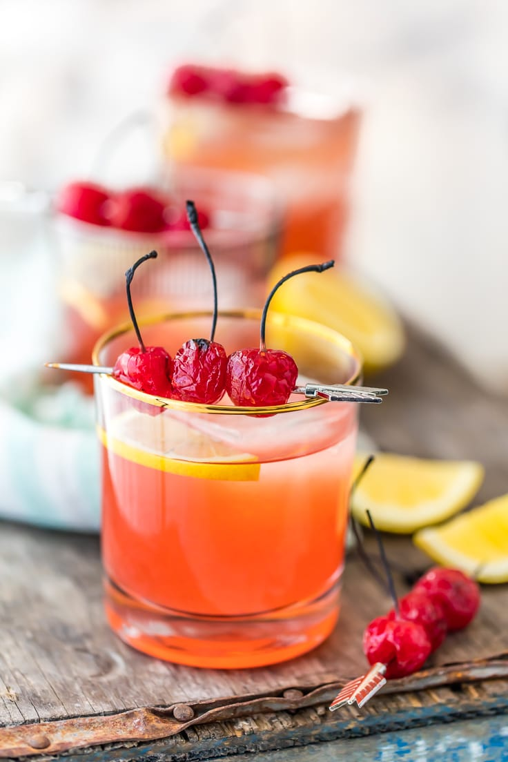 whiskey sours garnished with cherries and sliced lemons