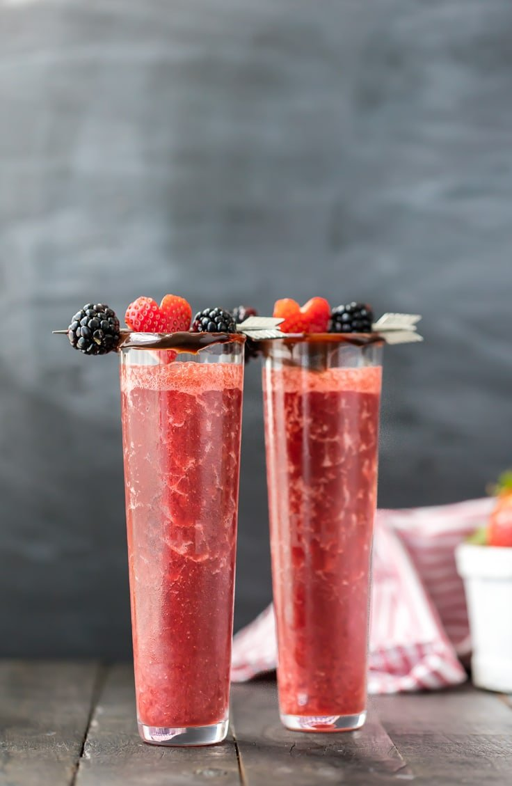 two tall skinny glasses filled with chocolate covered strawberry wine cocktail and topped with berries