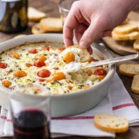 Goat Cheese Dip filled with cherry tomatoes, basil, garlic, and more is my FAVORITE EASY CHEESE DIP APPETIZER! It's classy, it's simple to make, and it's so delicious. Serve this baked cheese dip hot with some crostini, toasted bread, or hearty crackers.