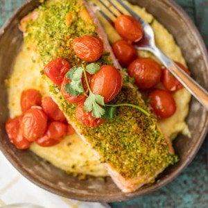 Herb Crusted Salmon with Goat Cheese Polenta is our favorite easy salmon recipe! This crusted salmon has so much flavor, and when mixed with roasted tomatoes and cheesy polenta, it makes the perfect healthy salmon and polenta meal.