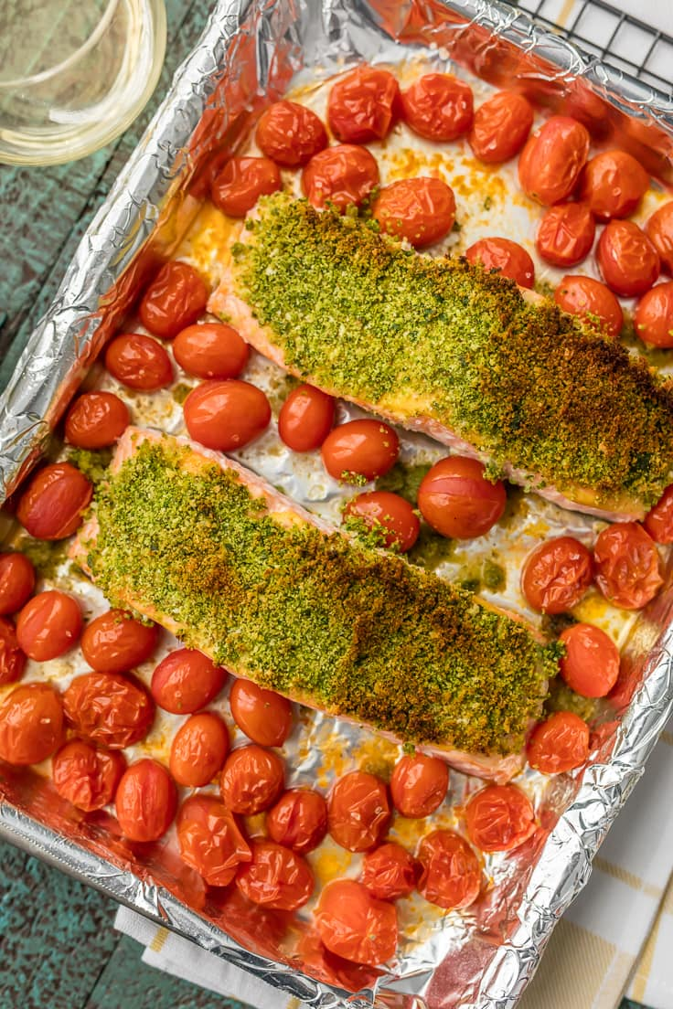 herb crusted salmon surrounded by cherry tomatoes on a baking sheet