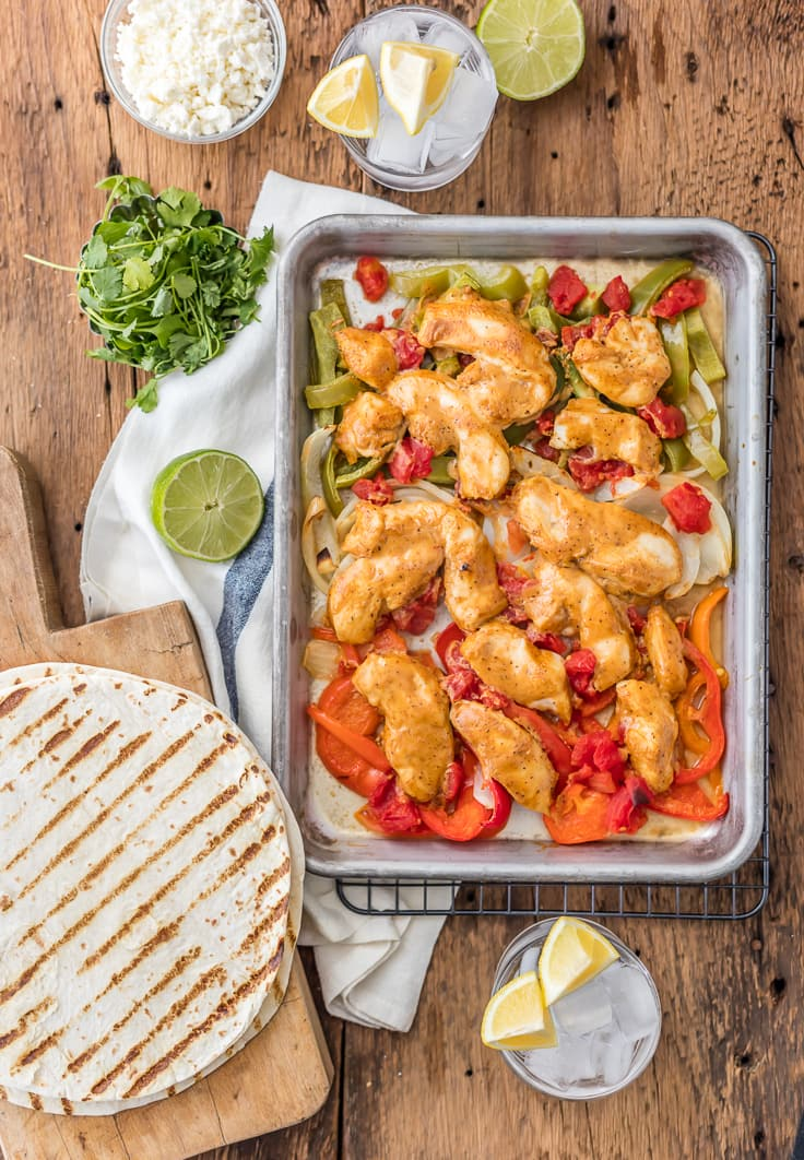 sheet pan chicken fajitas on a wooden table, surrounded by tortillas, drinks, and bowls of ingredients