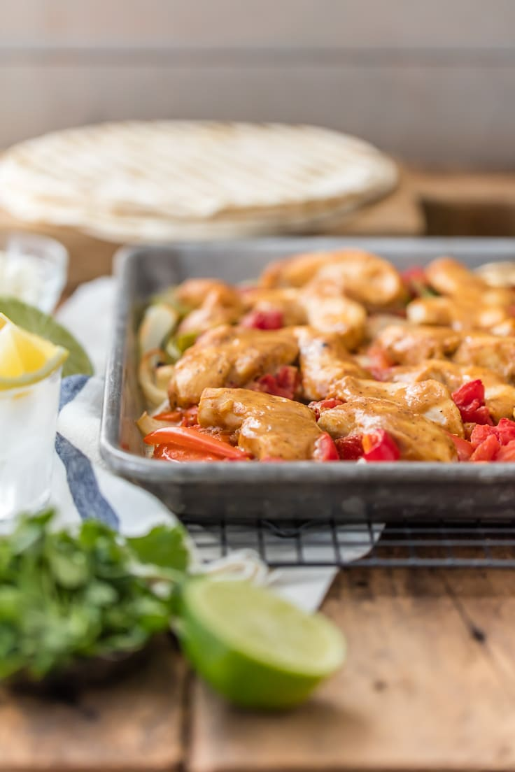 side view of a sheet pan full of baked chicken fajitas