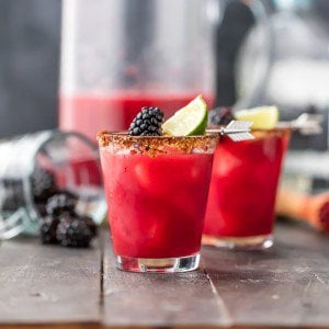 two spicy blackberry margaritas garnished with fruit