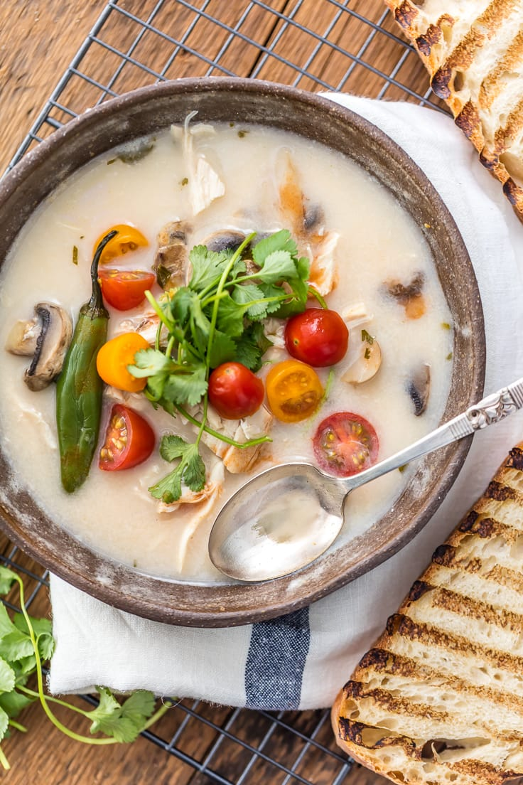 bowl of soup with mushrooms, tomatoes, chllis, cilantro, and more