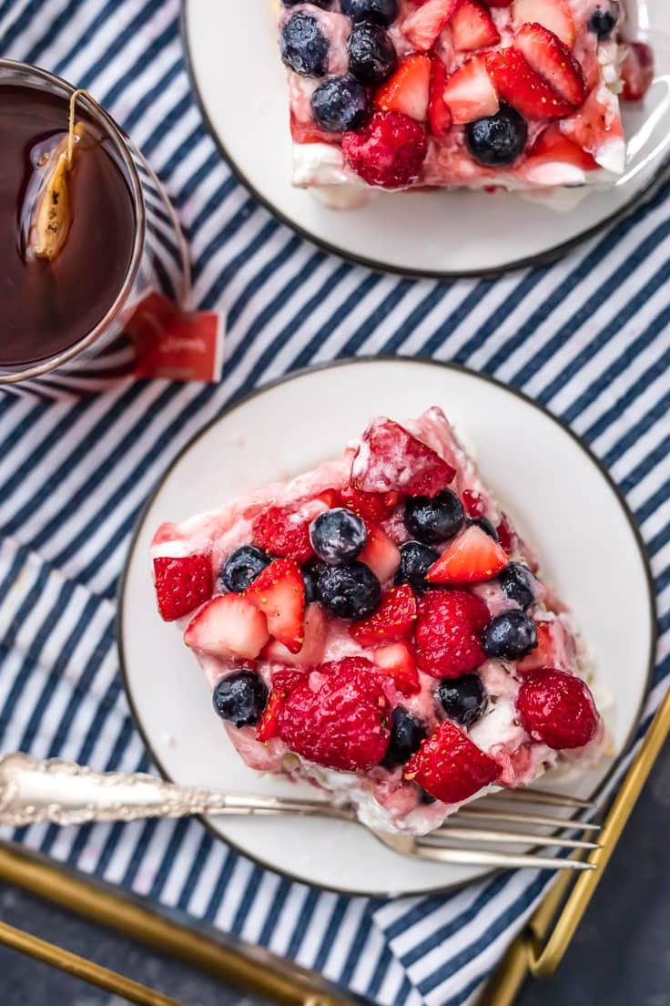 two plates of strawberry tiramisu with bluerberries and raspberries