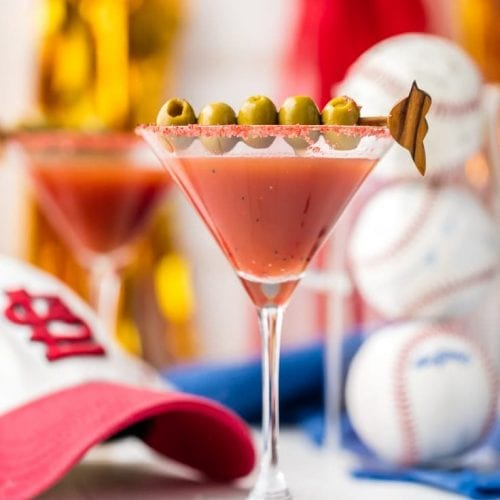 dirty redbird martini in a glass garnished with olives surrounded by baseballs and a saint louis cardinals hat