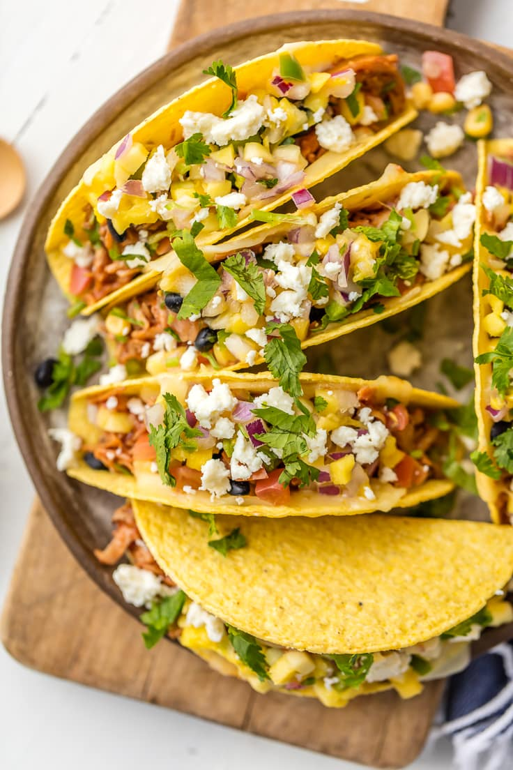 Slow Cooker Honey BBQ Chicken Tacos are our favorite easy family dinner! Top with mango, cilantro, black beans, and cheese for the perfect BBQ Chicken Tacos! SO DELICIOUS!