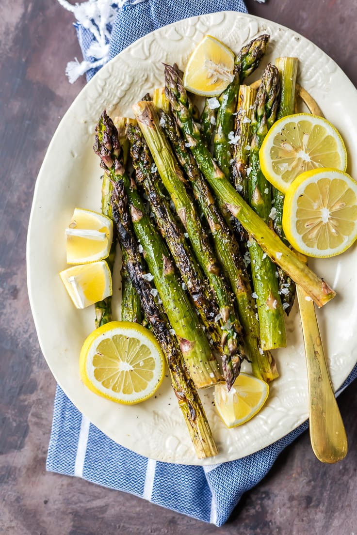 asparagus stalks and lemon slices on a white plate