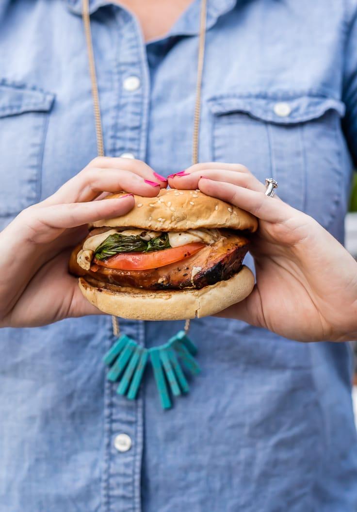 woman holding a chicken caprese sandwich