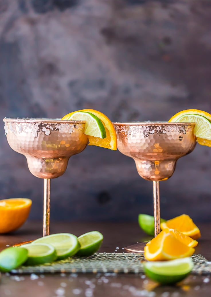 two margaritas surrounded by slices of lime and orange