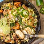 jerk chicken in a skillet with a fork