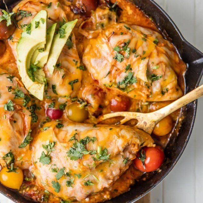 a top view of enchilada stuffed chicken in a skillet with wooden spoon