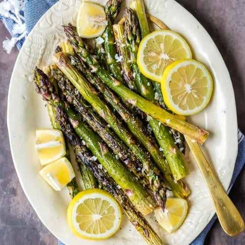grilled lemon butter asparagus on a plate with sliced lemons