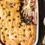 banana split dump cake in a baking dish with spatula