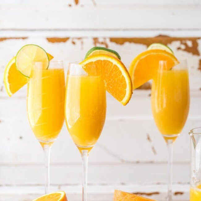 three moscow mule mimosas on a table with sliced oranges