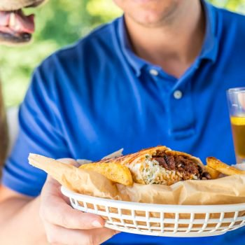 a man holding a basket that has a brisket burrito in it