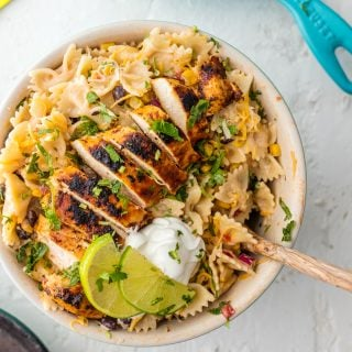 Chicken Enchilada Pasta Salad is bursting with flavor, super easy, and sure to please! Make it as indulgent or healthy as you'd like, you can't go wrong! Loaded with corn, beans, taco spiced chicken, onion, cilantro, and cheese. YES PLEASE!