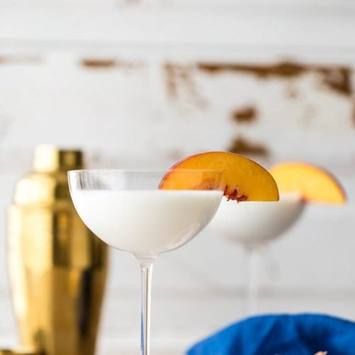 gooey butter cake martini with sliced peach on rim