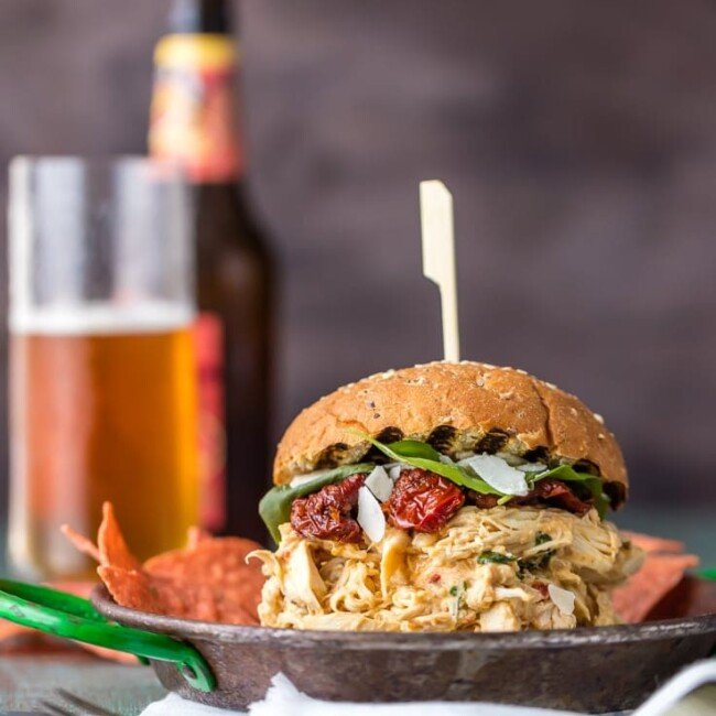 chicken alfredo sandwich on a plate with a beer in a glass behind it