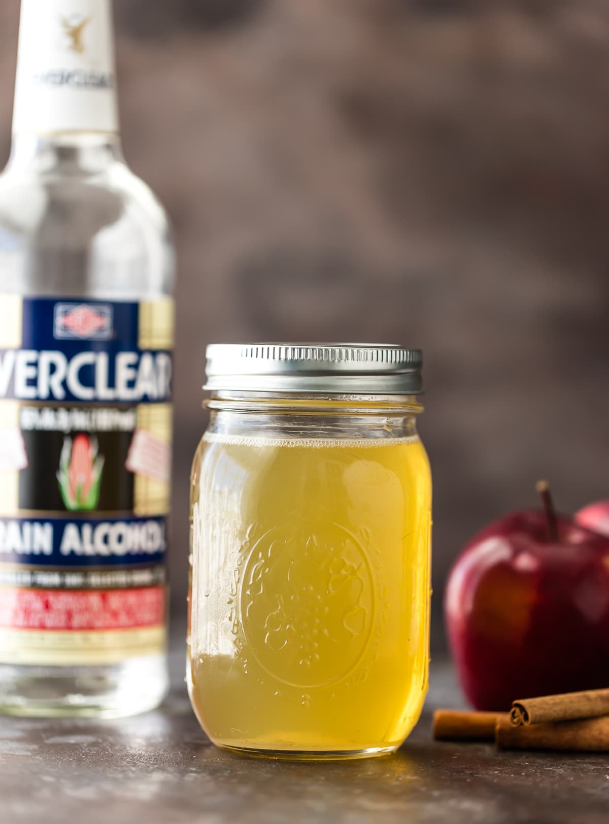 A jar of homemade apple vodka next to a bottle of everclear