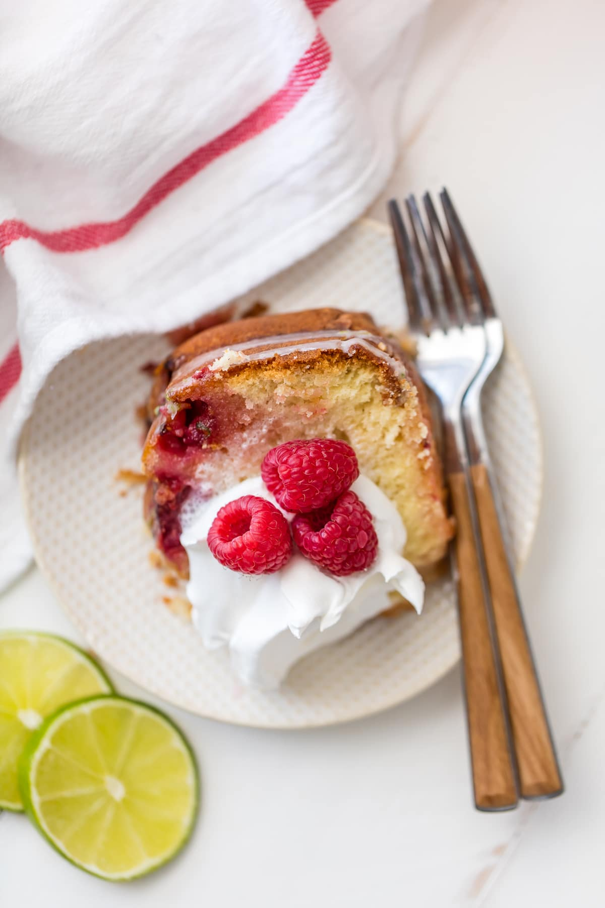 A slice of raspberry cake topped with cream and raspberries, on a white plate with two forks