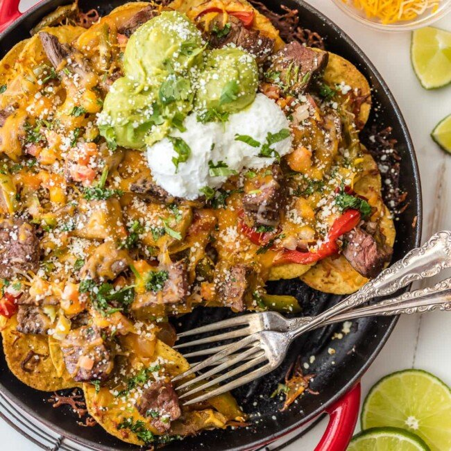 SKILLET STEAK FAJITA NACHOS are a must make for tailgating, the Super Bowl, or anytime! These delicious steak nachos are loaded with peppers, onion, cheese, and marinated steak. Possibly the best nachos ever!