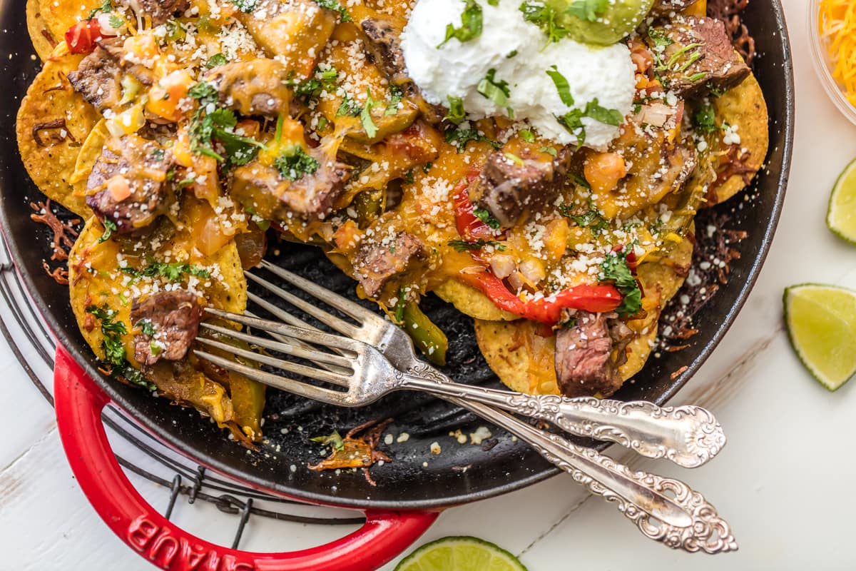 SKILLET STEAK FAJITA NACHOS are a must make for tailgating, the Super Bowl, or anytime! Loaded with marinated steak, peppers, onion, and cheese! BEST NACHOS EVER!