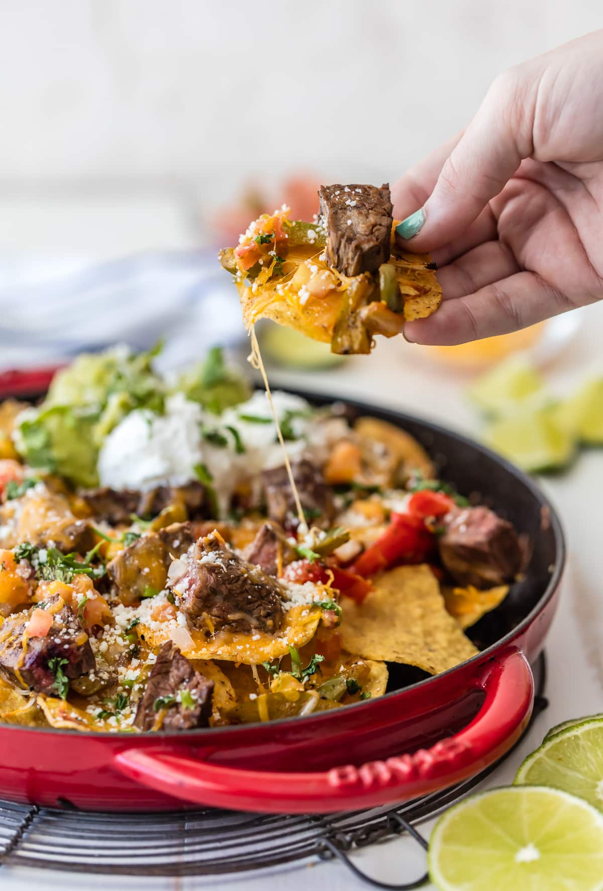 A skillet filled with nachos, topped with steak, cheese, peppers, and more