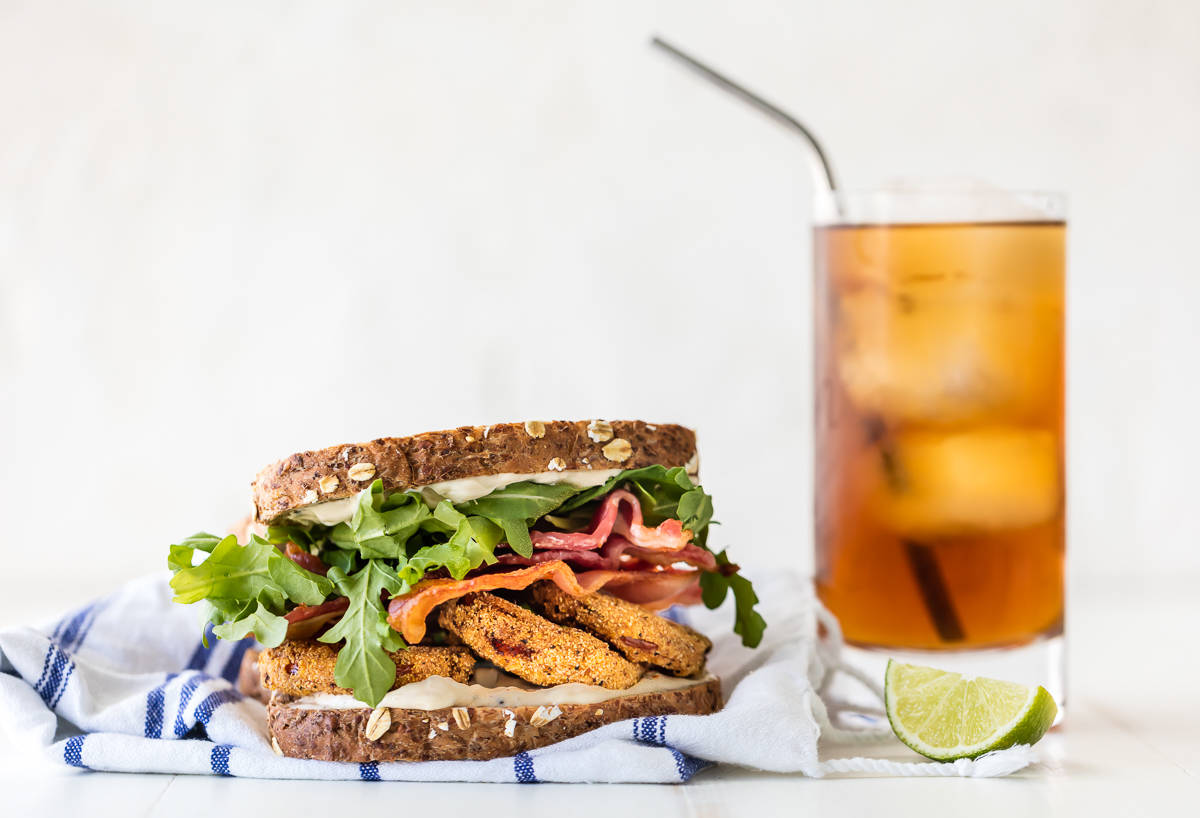 A blt sandwich on a dish towel next to a glass of sweet tea