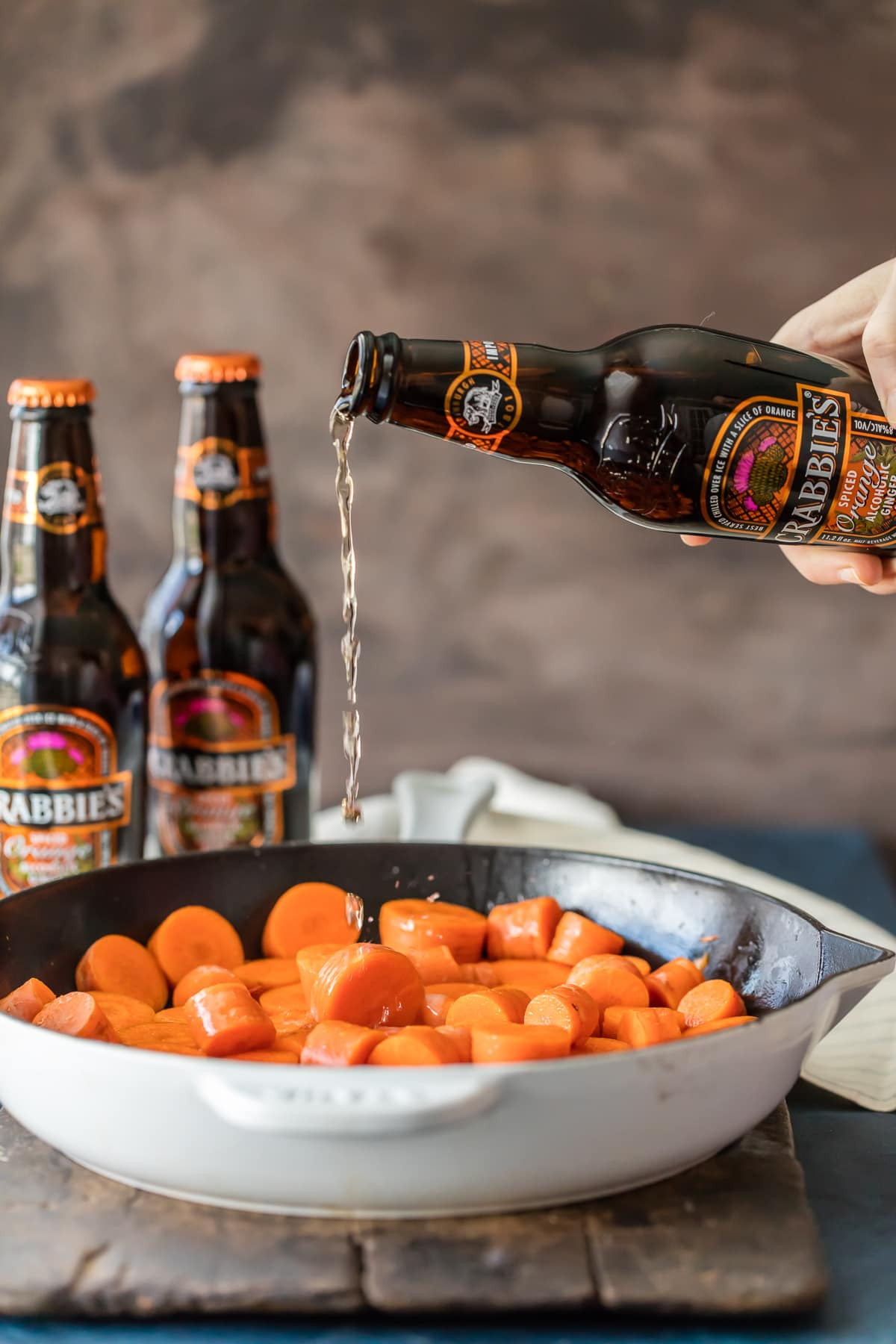 Pouring ginger beer over sliced carrots in a skillet